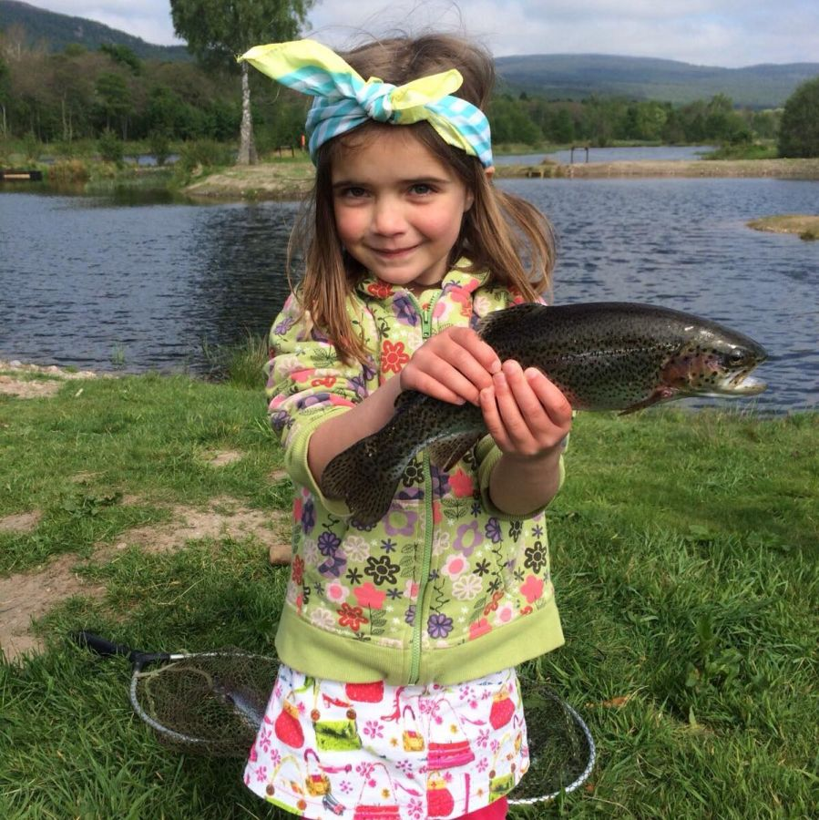 A young girl holding a fish at Rothiemurchus Fishery