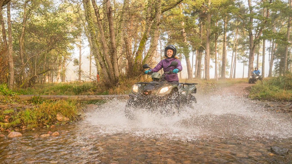 woman on quad bike driving through water